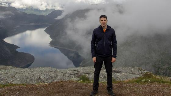 photo of young man standing in front of a Norwegian mountain landscape