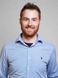 portrettbildet av en smilende ung man med en blå skjorte