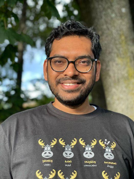 portrettbildet av en smilende ung man med solbriller