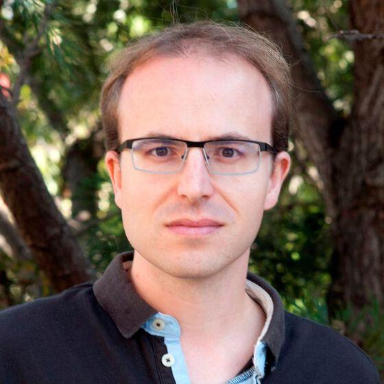 portrettbildet av en smilende ung man med briller