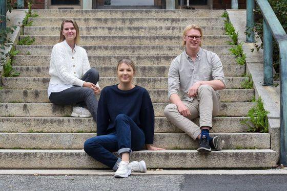 Foto av tre studenter satt på trappa