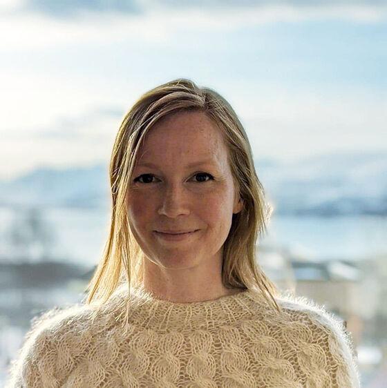 Ung kvinne med lyst hår og lys strikkegenser i Tromsø