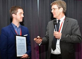 Mathew Domeier overrekkes Rauschmedaljen 2018 av Øystein Nordgulen på NGFs vinterkonferanse, Bergen 8.1.2019. Foto: Gudmund Løvø/NGU
