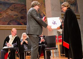 RESEARCH PRIZE: Professor Trond H. Torsvik gets applause from a full-packed audience in the University Aula when he gets the research award from the Deputy Rector Ragnhild H. Hennum. Rector at UiO, Ole Petter Ottesen and the Deputy University Director Tove Kristin Karlsen are seen in the background for the prize winner. Photo: Yngve Vogt, Apollon
