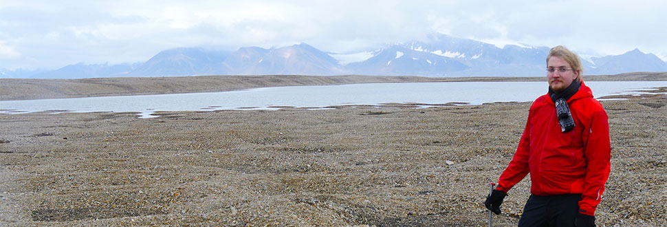 man stands in front of mountains at Svalbard