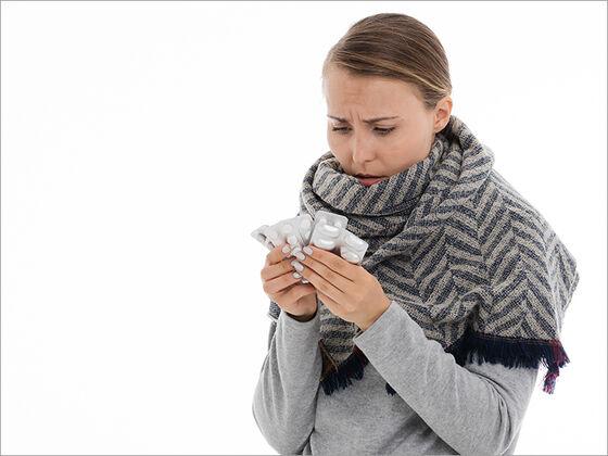 Kvinne som holder tre brett tabletter med en bekymret mine