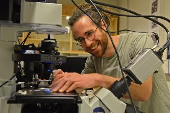 Smilende mann justerer mikroskop