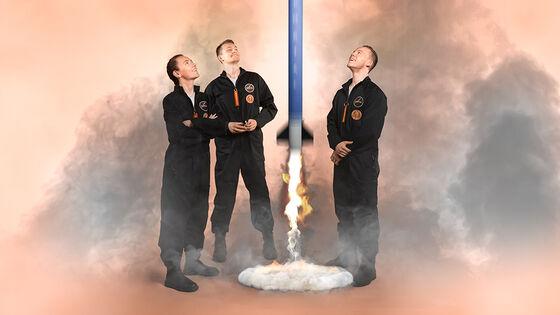 3 personer i arbeidsklær, rakett under oppskyting