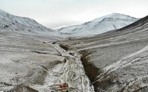 The Permian-Triassic boundary is outcropping in the stream bed of Deltadalen, Svalbard. A 100-meter-long core was drilled one kilometer south of the outcrop in 2014, recovering the boundary interval. The Grusryggen mountain in the background. View to the south. (Photo: Julian Janocha.