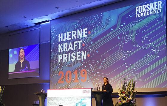 Leder for Forskerforbundet Guro Lind offentliggjør vinnerne av Hjernekraftprisen 2019 på det forskningspolitiske seminaret den 12.11.19 på Radisson Blu Scandinavia, Oslo. Foto: Forskerforbundet