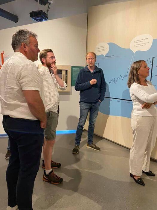 Fire personer utforsker en graf på en vegg på Norsk Fjellsenter.