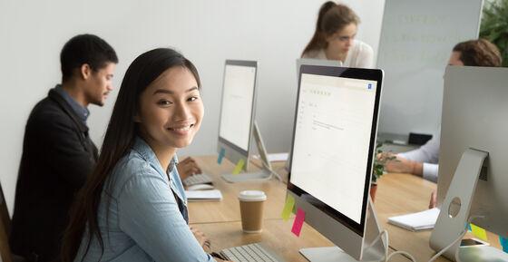 Smilende ung kvinne foran en dataskjerm.
