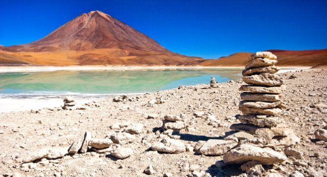 A stack of stones by a lake and a red mountain.
