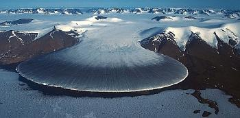 A glacier flowing out from a mountain range.