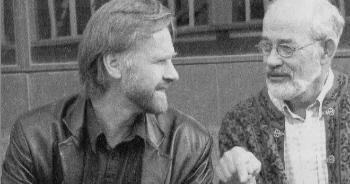 A black-and-white photo of two men having a discussion.