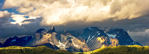 Mountain range with green in the front and cloudy sky in the background.