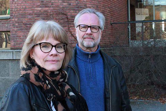 to personer står foran en bygning, ser i kamera