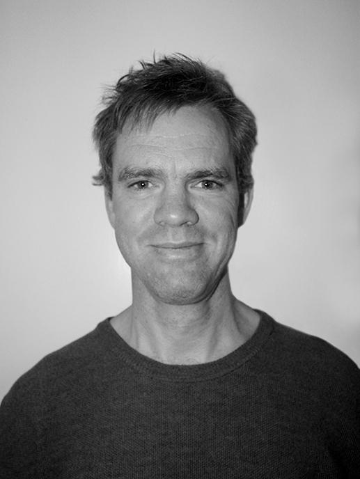 Svart-hvitt bilde av smilende mann med kort, grått hår