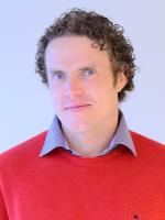 Mann med rødlig krøllete hår og rød genser