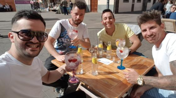 Four men sitting at a coffee table at a plaza in Spain
